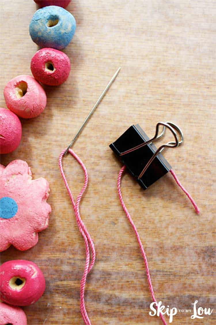 threaded needle with binder clip on end of string
