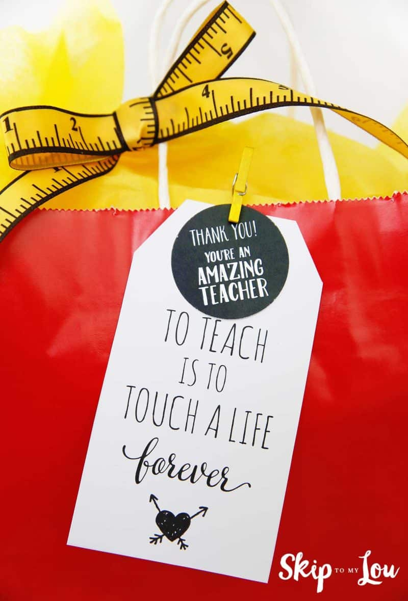 to teach is to touch a life tag clipped to a red gift sack