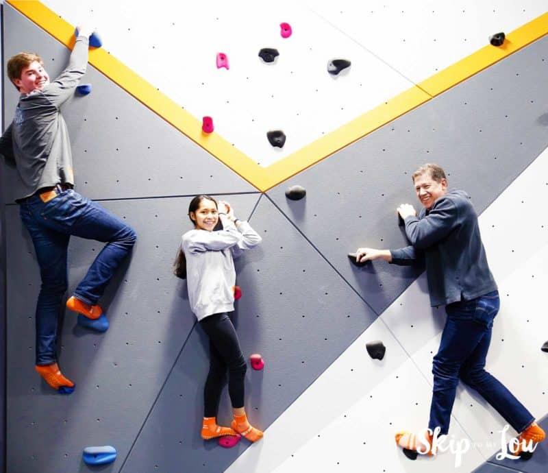 three people wall climbing