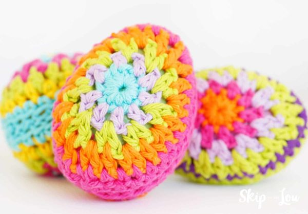 crochet egg with bright pink, orange, yellow, light pink, and light blue rings yarn