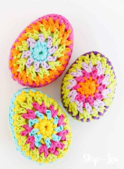 three crochet granny square pattern eggs on white background