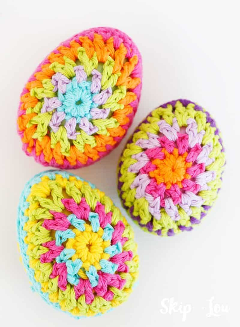 three crochet granny square pattern eggs on white background