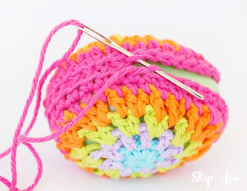 sewing crochet egg together with yarn needle