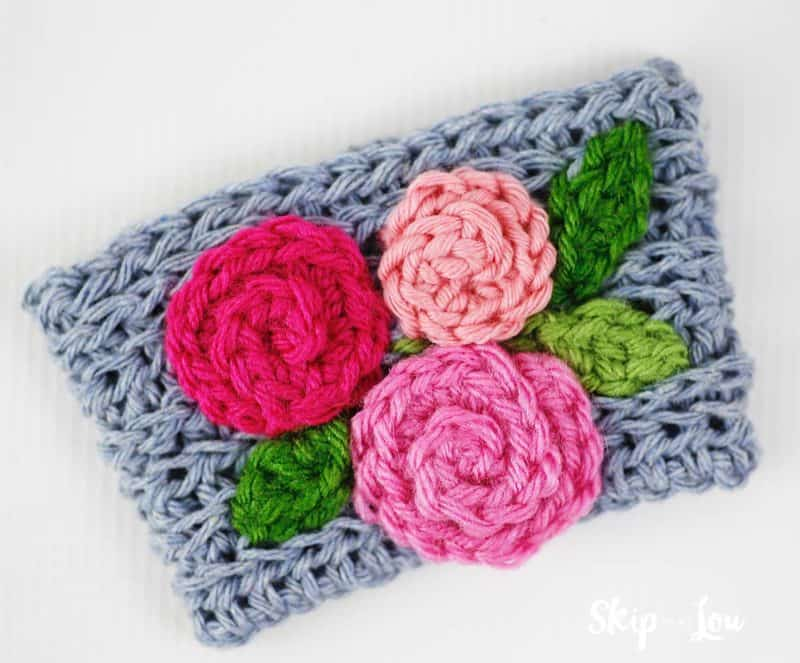 gray crochet coffee cozy with pink flowers and green leaves