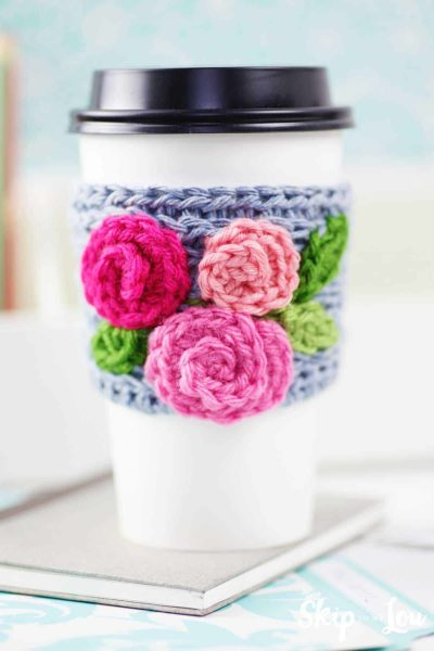 crochet coffee sleeve with roses on white take out cup sitting on desk