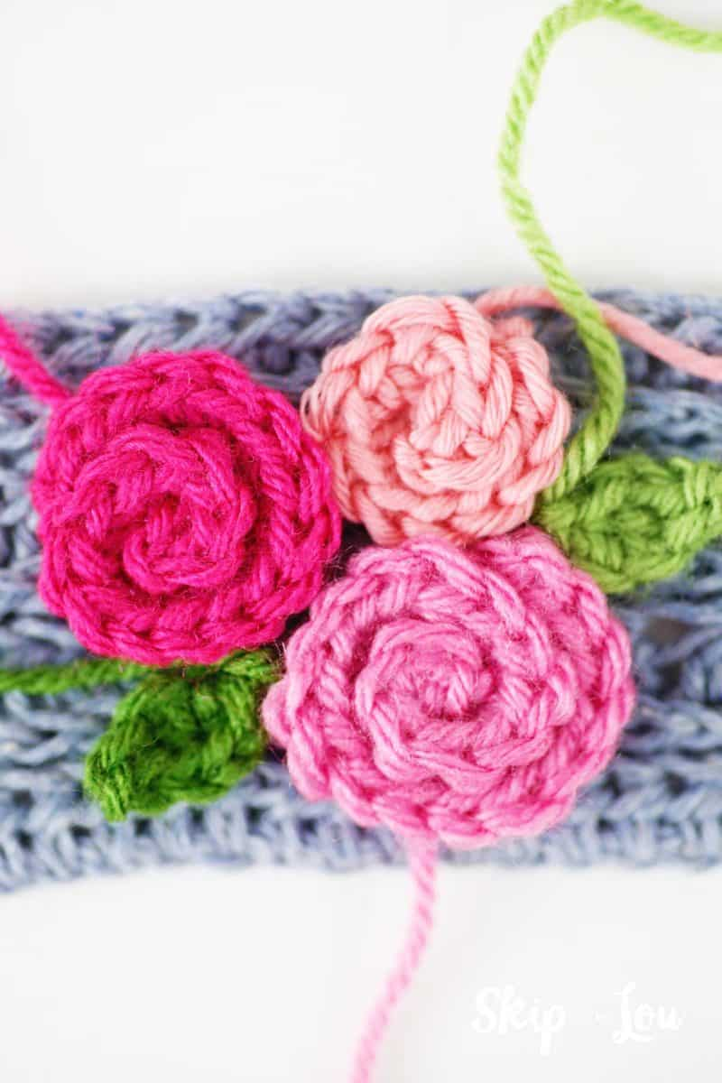 placing flowers on crochet coffee cozy