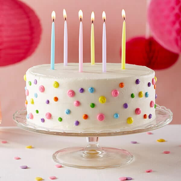 polka dot birthday cake on cake stand with lit candles