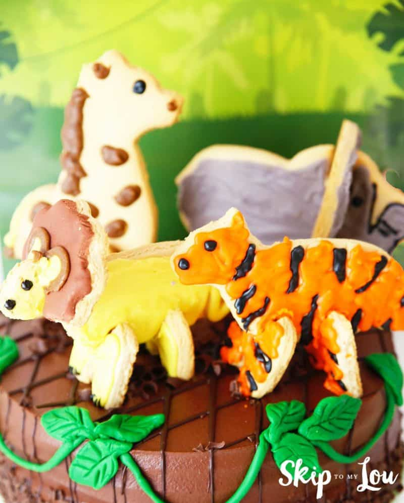 giraffe lion tiger and elephant cookies on cake