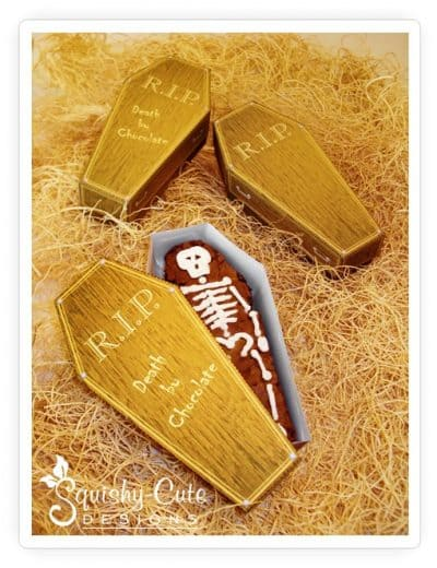 Three coffin treat boxes with skeleton chocolate treat inside by Squishy-Cute Designs; the coffin is made from a printable template
