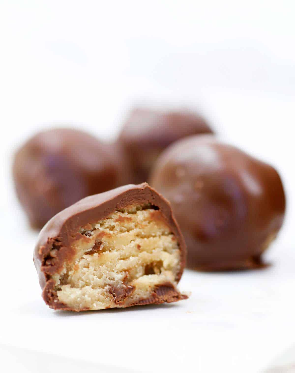 set and ready to eat cookie dough truffles; a truffle is cut in half showing the outer chocolate layer and creamy cookie dough middle