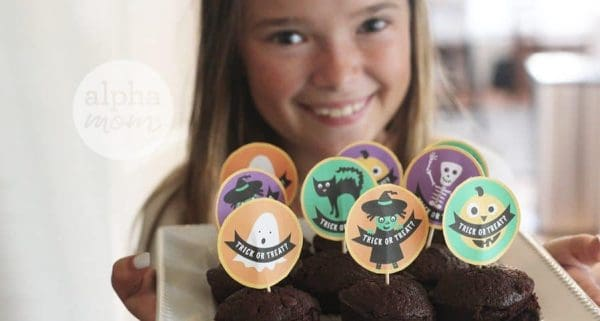 printable vintage ghost, witch, pumpkin, black cat, skeleton cupcake picks on chocolate cupcakes; the plate of cupcakes is being held by a little girl