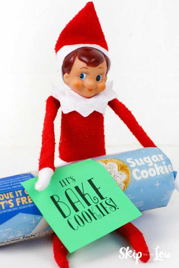 "elf on the shelf holding cookie dough with note ""Let's bake cookies"""