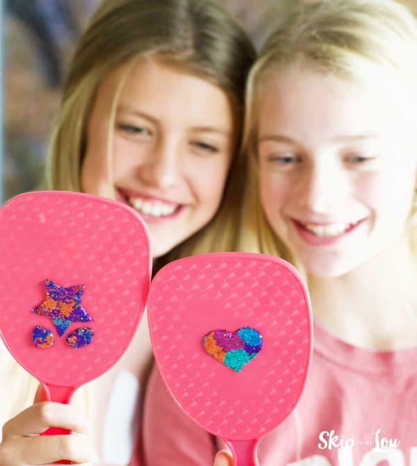 two girls holding glitter decorated hand held mirrors
