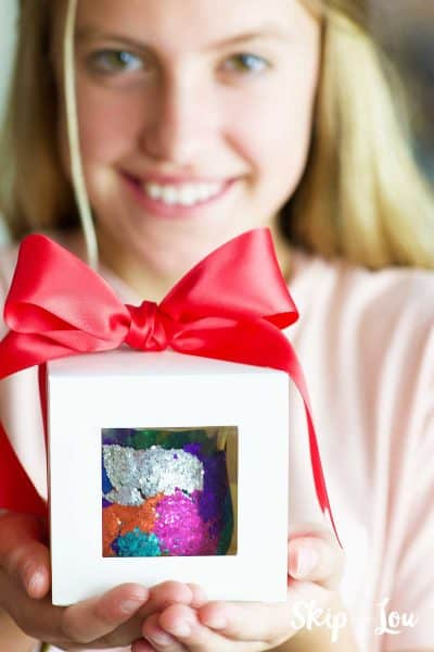 girl holding box with bow holding glitter votive