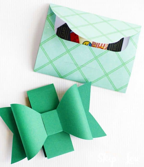 paper bow sitting beside paper gift card holder template