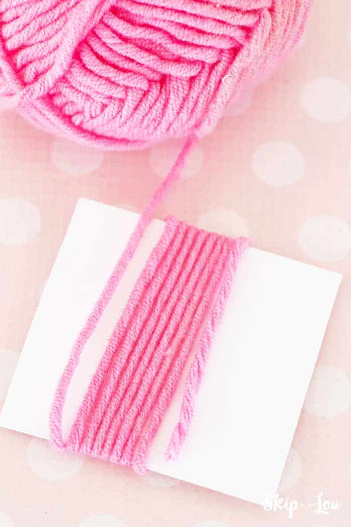 yarn ball yarn wrapped around white card to make DIY tassel