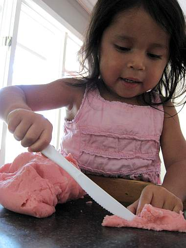 child cutting playdough
