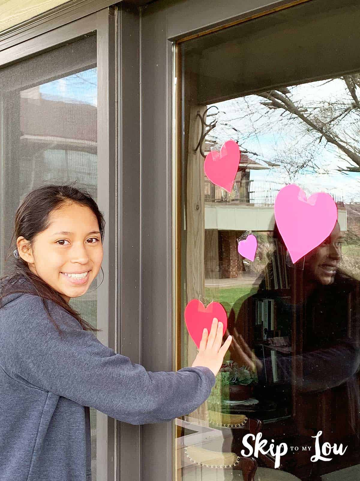 child placing hearts on window of shut in