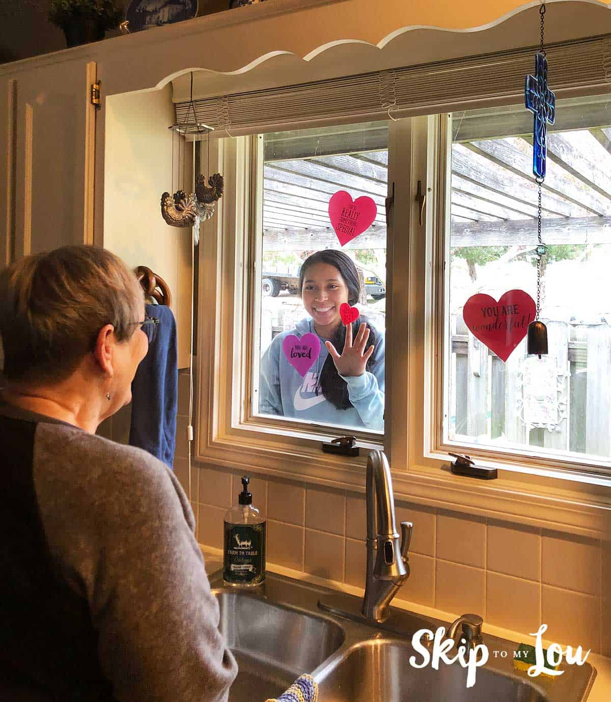 senior looking at child through window with hearts