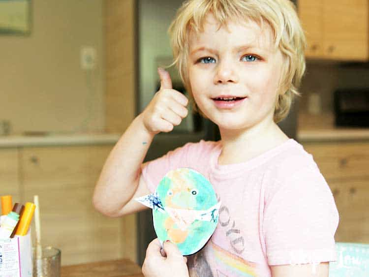 child giving thumbs up holding paper egg chick