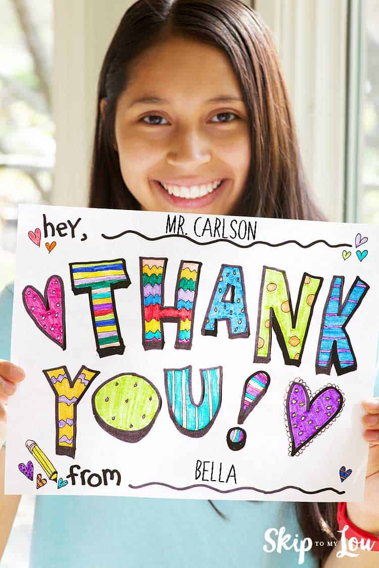 girl holding colored thank you coloring page sign