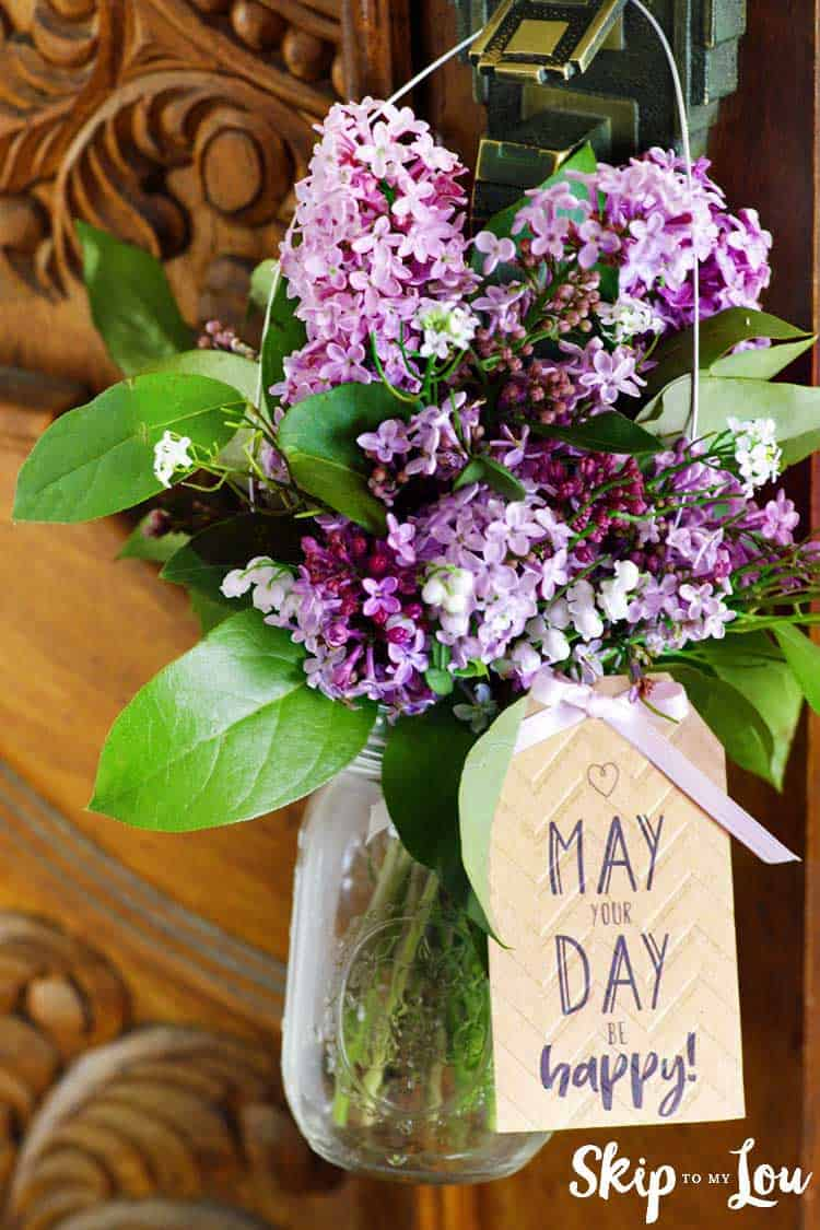 mason jar filled with flowers hanging on door with tag that says may your day be happy