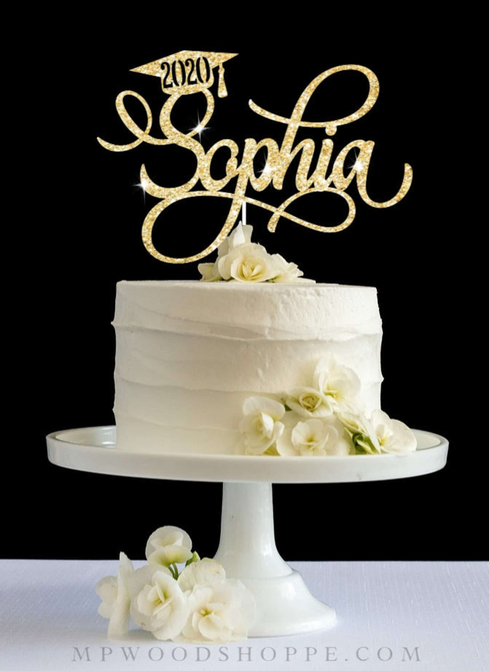white frosted cake with gold glitter acrylic graduation cake topper on white cake stand
