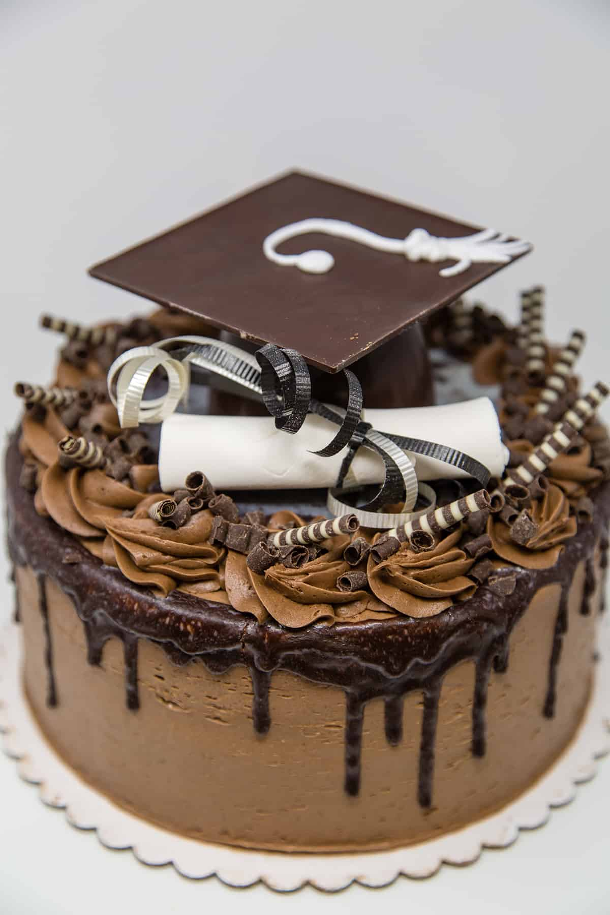 round cake covered in chocolate ganache with fondant diploma and chocolate grad cap