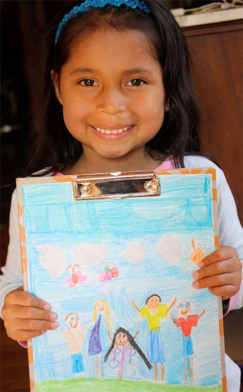 child holding embellished clipboard