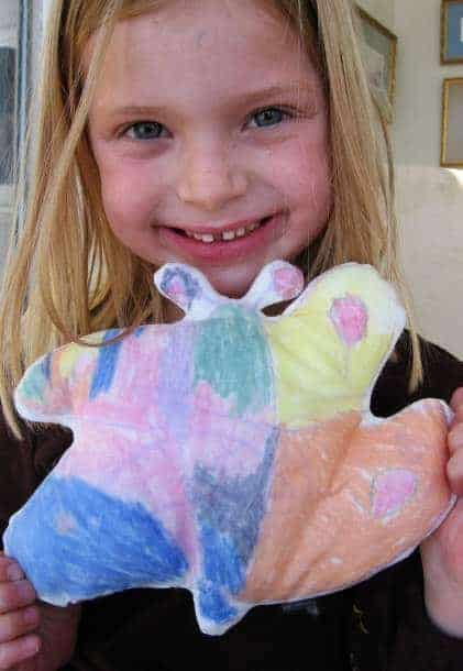 child holding stuffed butterfly made from child's drawing