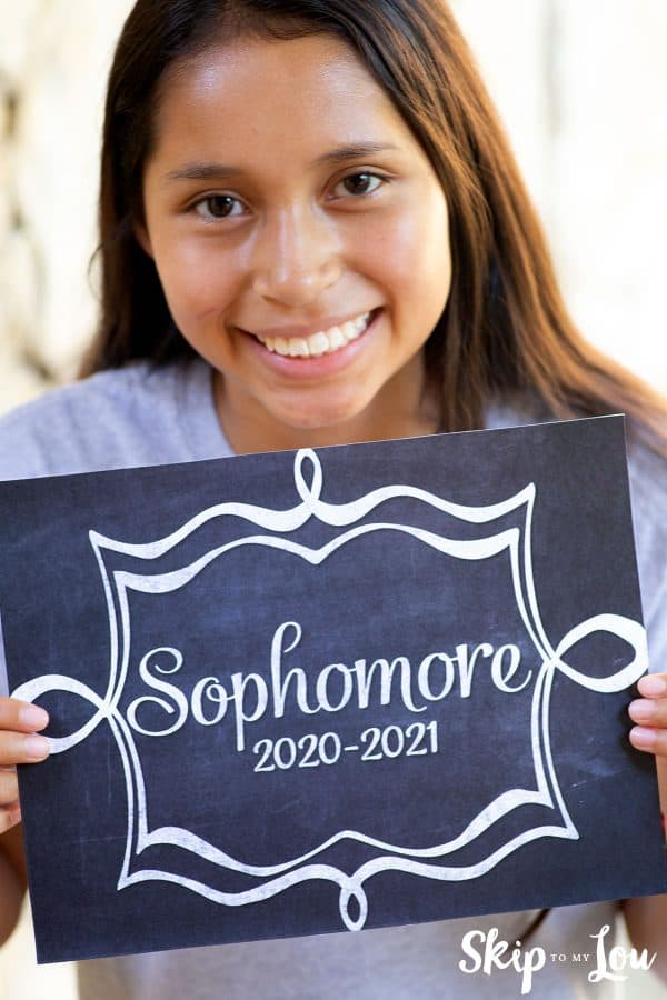 girl holding sophomore back to school sign