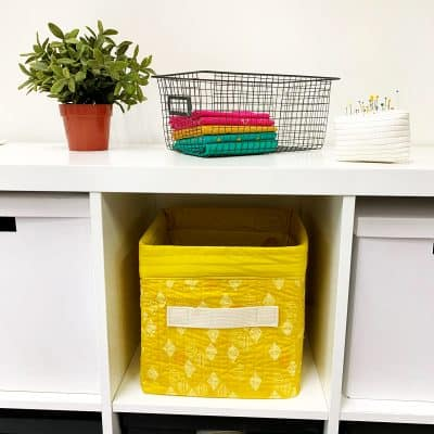 White shelf displaying a quartz gold fabric storage with taupe handles on the side; this bin is all fabric and stitching