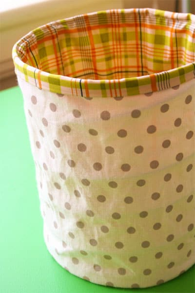 A fabric spring-form bucket with cream and tan polka dot exterior fabric and line with a cream, spring green and pink plaid fabric lining