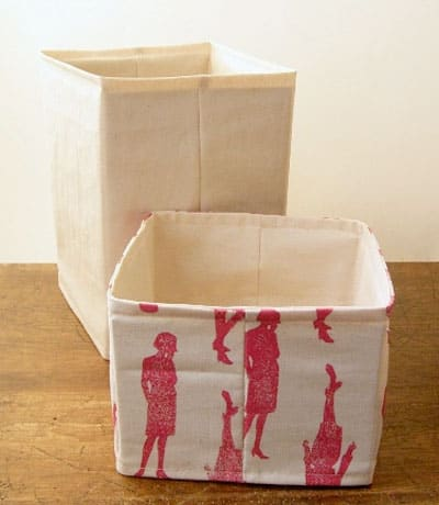 Two canvas fabric boxes, one is taller and the fabric is plain; the second is shorter and the fabric has a pink silhouette of a woman in a dress on it