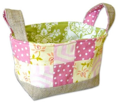 Pretty fabric basket that has pink and white polka dot, yellow floral, yellow with pink lines fabric squares sewn together, with a green and white fabric lining the inside of the basket with a canvas bottom and canvas and pink polka dot handles