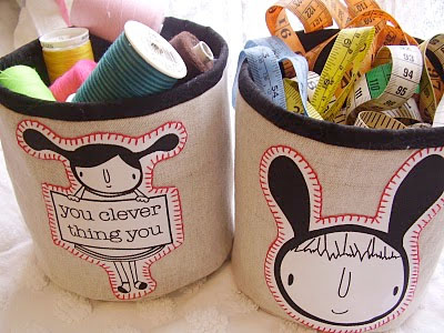 Two round fabric buckets, exterior fabric is canvas or beige colored fabric and the lining and trim are brown. Both buckets are decorated with hand decorated art the one is a girl  in pig tails holding a sign that says, you clever thing you;' the other is decorated with the image of a boy;s head with a hood with ears