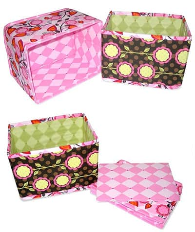 Two collapsible fabric bins one has a pink leafy outer fabric with a pink harlequin fabric lining; the second has a brown polka dot fabric with pink, yellow and green flowers on it, it is lined with foam green harlequin fabric