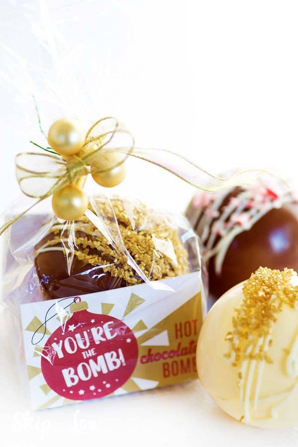 packaged cocoa bomb with printable label and cellophane bag with cocoa bomb topped with gold sanding sugar