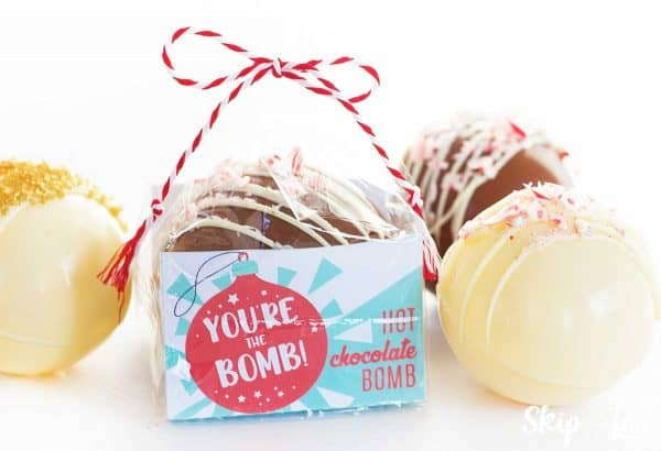 packaged cocoa bomb with white chocolate cocoa bomb topped with peppermint pieces sitting beside