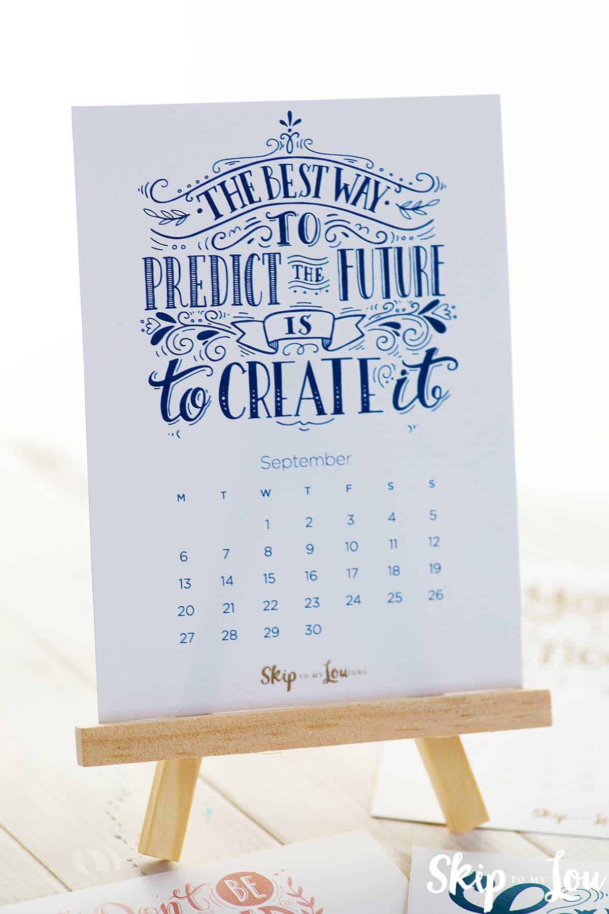 tiny printable 2021 calendar with inspirational saying the best way to predict the future is to create it, sitting on wooden easel