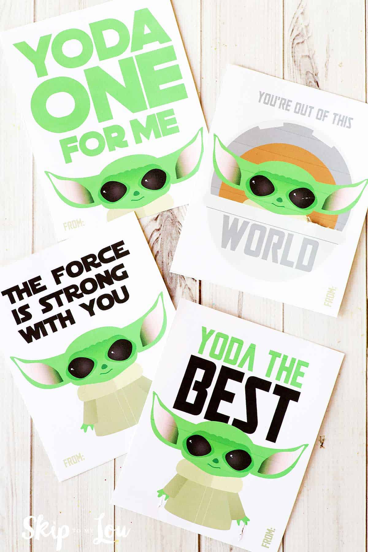 four printable baby Yoda valentines on white wood background