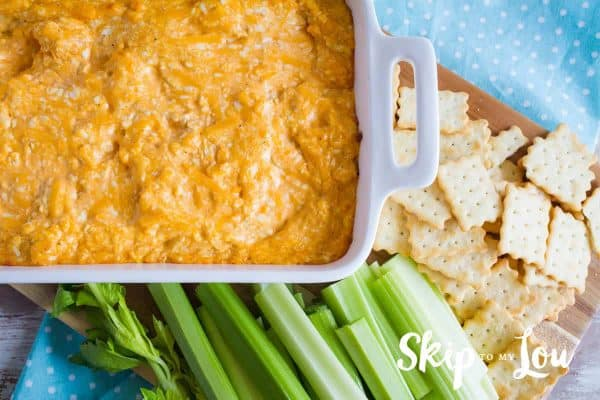 Buffalo chicken dip in a white casserole with crisp celery and crackers
