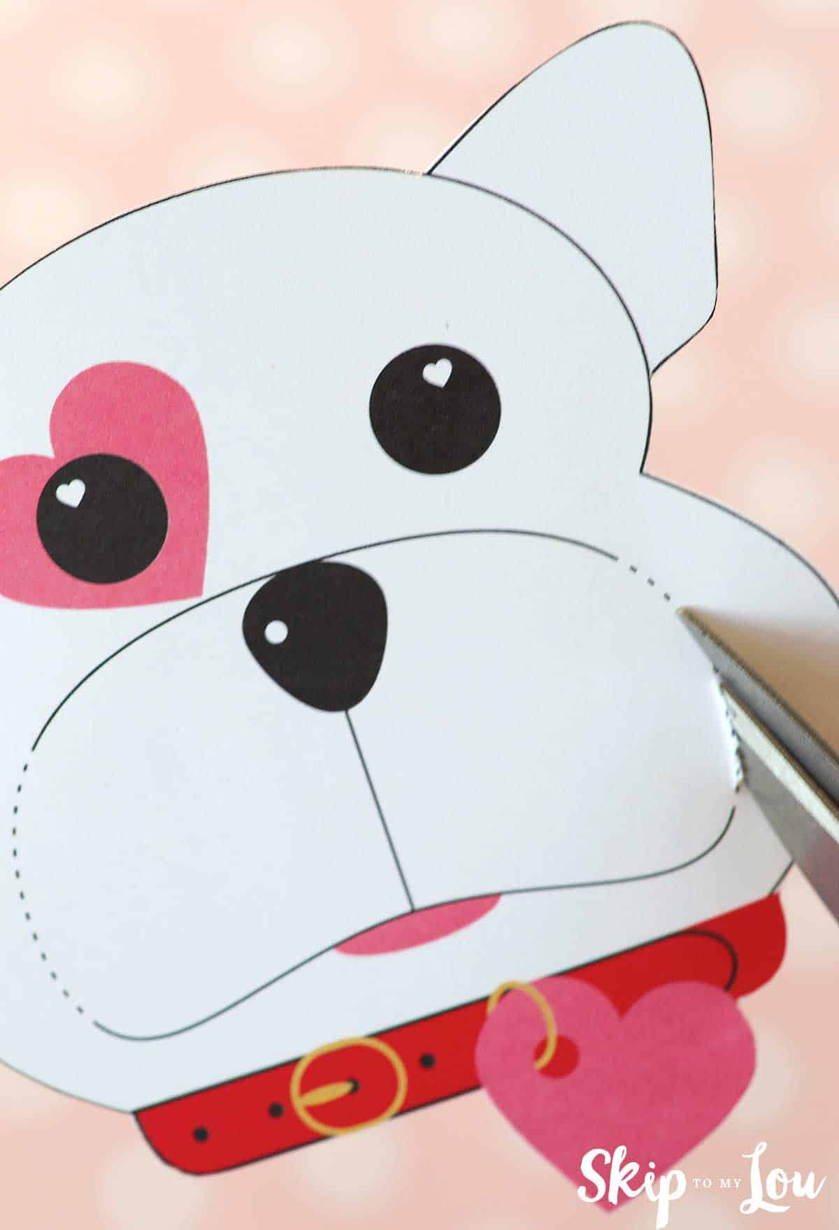 dog valentine cutting slits along dotted lines at side of mouth