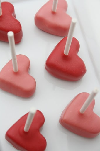 red and pink heart cake pops on white plate