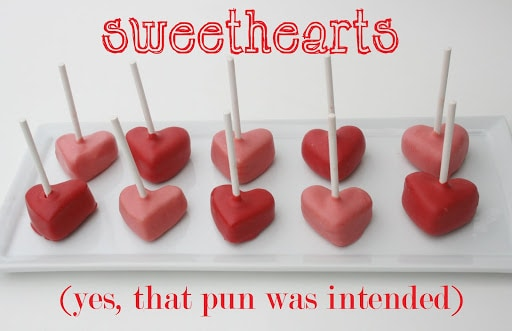 red heart cake pops on lollipop sticks on white place
