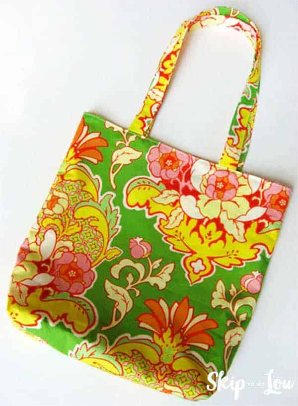 gift idea floral patterned reversible tote, the fabric is vibrant green, yellow, red, and pink