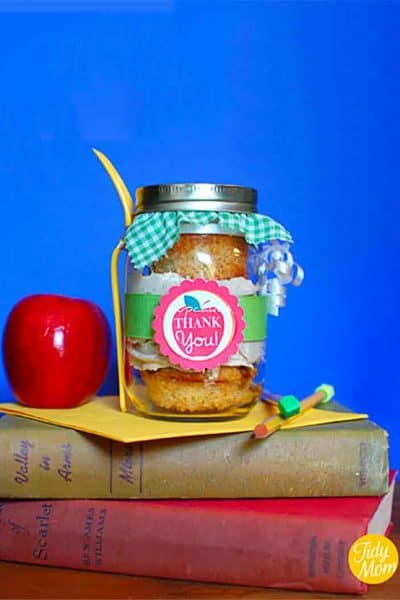 cupcakes in a jar with an apple thank you free printable tag wrapped the jar, the lid has a piece green gingham printed fabric over the top and a plastic fork is attached to the jar; this is reting on two books, and a card with a red apple to the left and pencil to the right