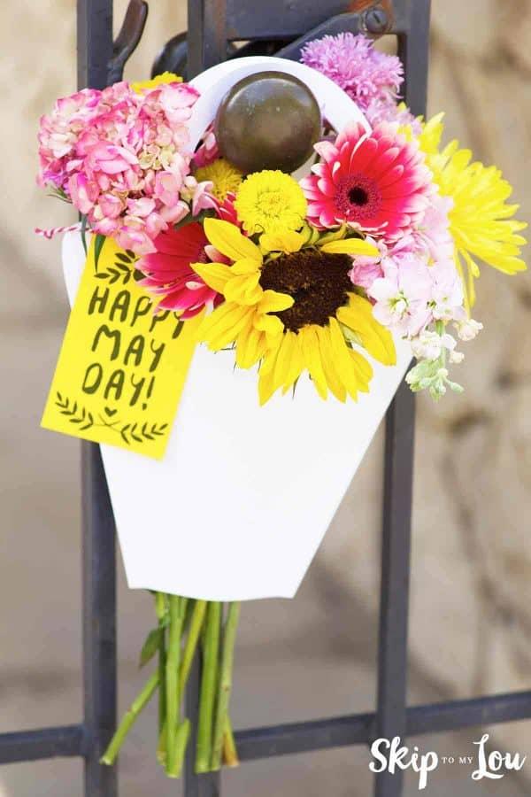 paper flower sleeve filled wit flowers hanging on door