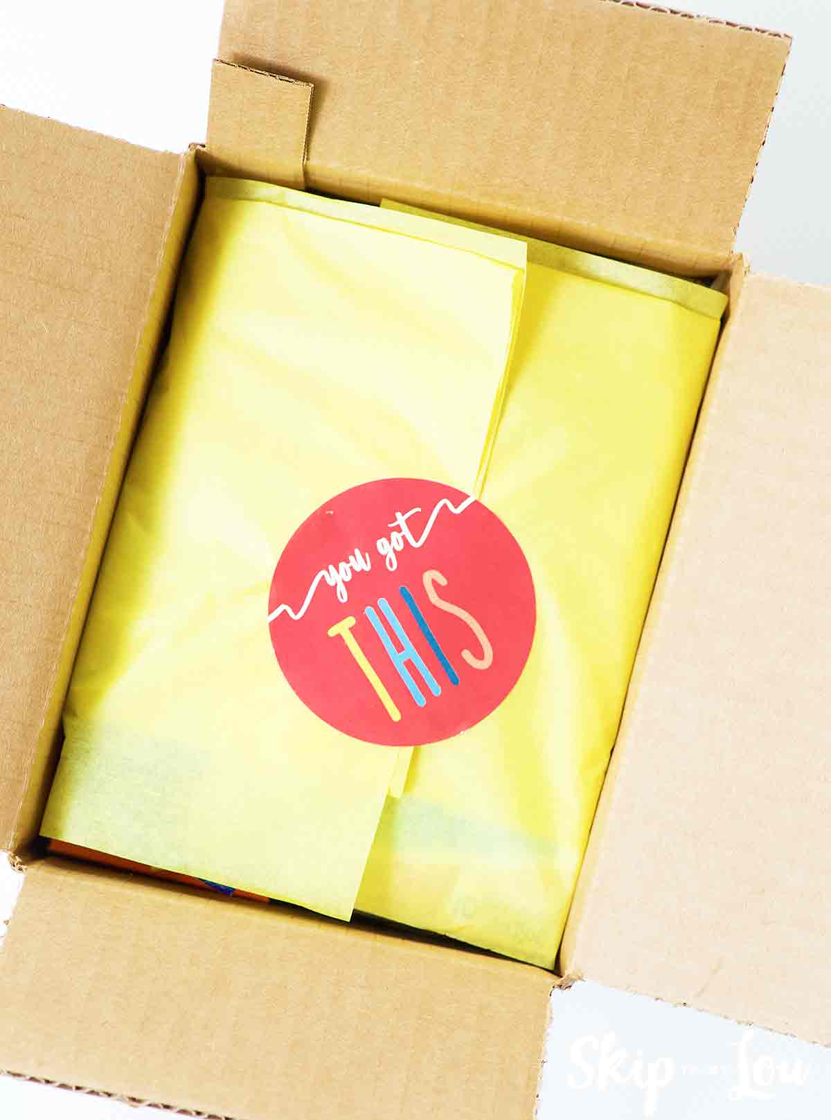 box lined with yellow tissue with red sticker that says you got this to make a care package