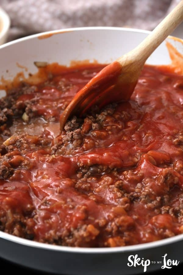 pasta sauce added to the browned ground beef in a skillet